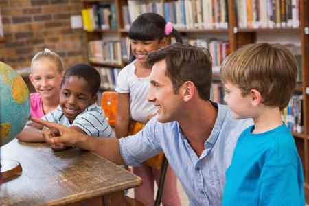 maestra ense�ando: Alumnos lindos y profesor que miran el globo en la biblioteca de la Escuela Primaria Foto de archivo