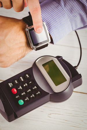 eftpos: Man using smart watch to express pay on a wooden table Stock Photo