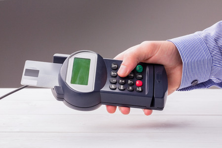 commercial activity: Man entering his pin on terminal on a wooden table Stock Photo