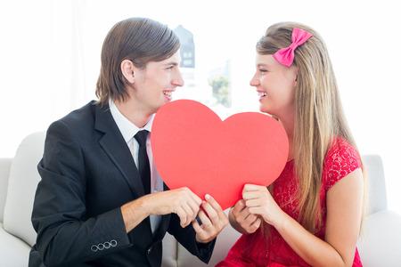 together with long tie: Pareja geek lindo sonriente y la celebraci�n de coraz�n en el sof�