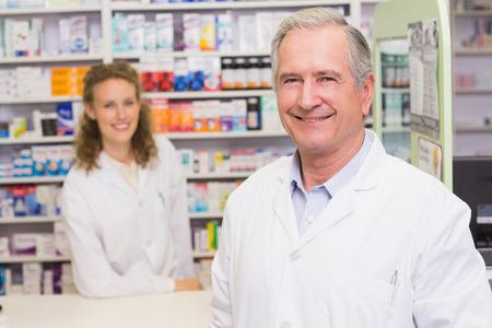 pharmacist: Smiling pharmacists looking at camera at pharmacy Stock Photo