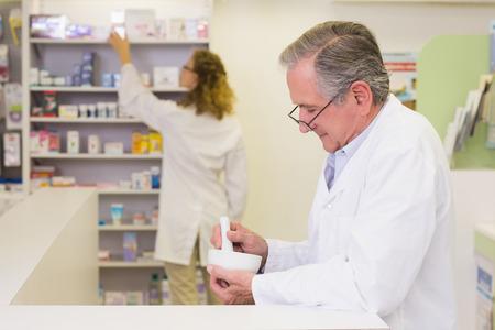 pharmacist: Senior pharmacist mixing a medicine at the hospital pharmacy