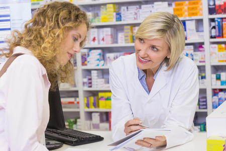 Pharmacist showing prescription to a customer at pharmacy