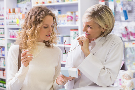 Pharmacist explaining medicine to his customer in the pharmacy