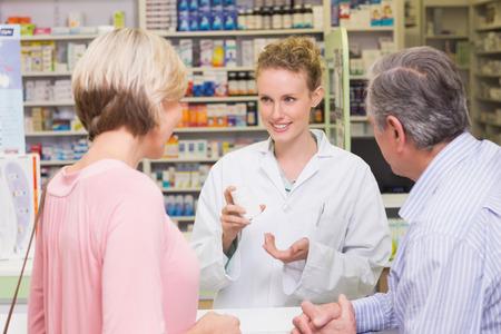 Farmacéutico y cliente enfermo hablar en la farmacia