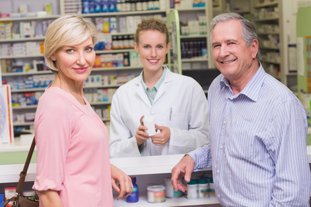 costumers: Pharmacist and costumers smiling at camera at pharmacy Stock Photo