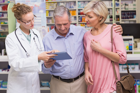 costumers: Pharmacist showing tablet pc to costumers at pharmacy Stock Photo