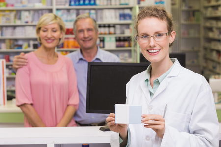 medicine box: Pharmacist holding medicine box at pharmacy