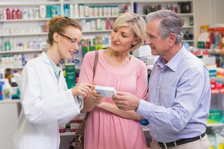 drugstore: Farmacéutico que explica la droga a clientes en farmacia Foto de archivo