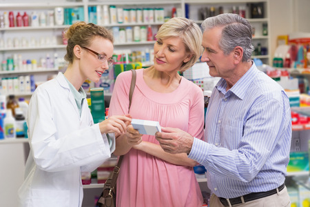 costumers: Pharmacist explaining the drug to costumers at pharmacy