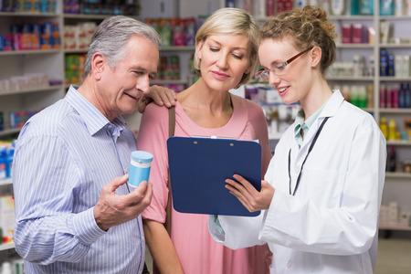 Pharmacist showing clipboard to costumers at pharmacy Stock Photo