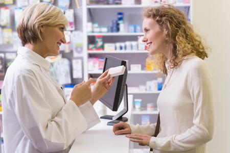 farmacia: Farmac�utico que sostiene caja de la medicina habla con el cliente en la farmacia
