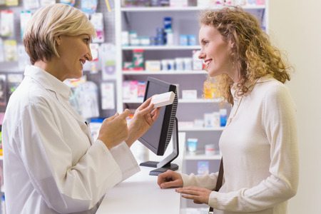Pharmacist holding medicine box talking to customer in the pharmacy