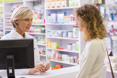 Pharmacist explaining the drug to patient in the pharmacy