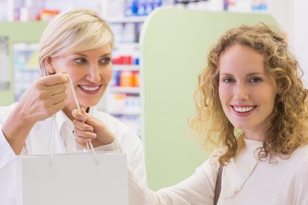 costumer: Pharmacist and costumer holding paper bag at pharmacy
