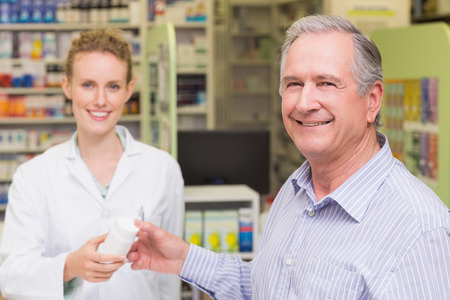 costumer: Pharmacist and costumer smiling a camera at pharmacy Stock Photo
