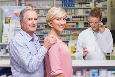 costumers: Costumers smiling to camera at pharmacy Stock Photo