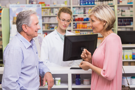 costumers: Costumers talking to each other at pharmacy Stock Photo