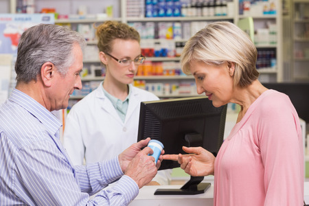 costumers: Costumers talking about medicine at pharmacy Stock Photo
