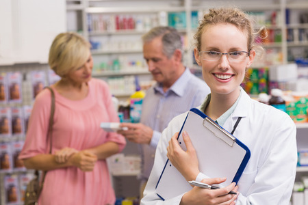 Pharmacist holding clipboard at pharmacy