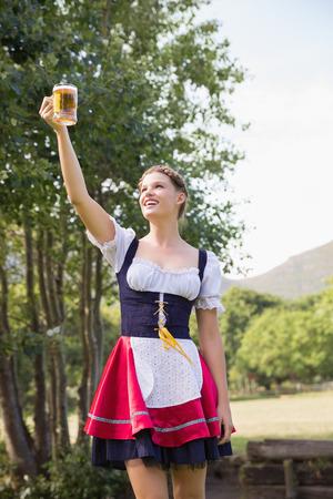 tankard: Pretty oktoberfest girl holding beer tankard on a sunny day