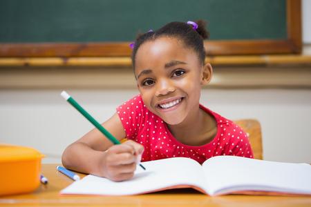 escuela primaria: Alumnos lindos que escriben en el escritorio en el aula en la escuela primaria