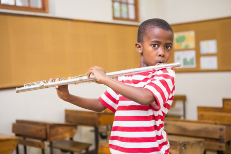 early childhood: Cute pupil playing flute in classroom at the elementary school Stock Photo
