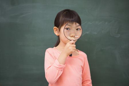 глядя на камеру: Ученик ищет камеру с увеличительным стеклом в начальной школе
