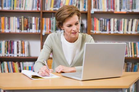persona escribiendo: Escritura del profesor en el bloc de notas en la biblioteca de la Escuela Primaria