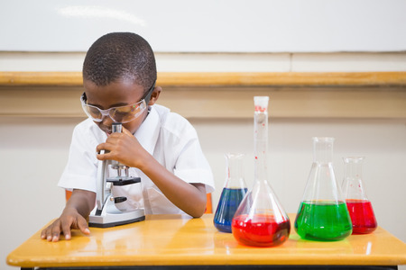 early childhood: Pupil looking through microscope at the elementary school