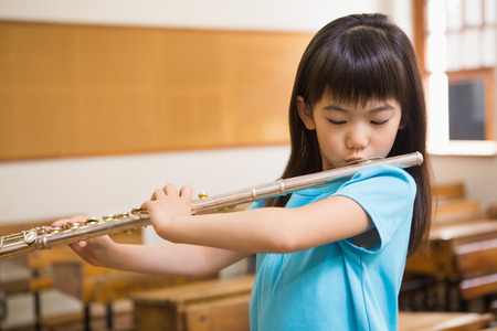 Cute pupil playing flute in classroom at the elementary school Stock Photo