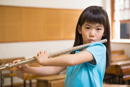 Cute pupil playing flute in classroom at the elementary school Imagens