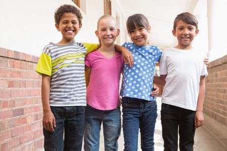 trato amable: Amigos felices sonriendo a la c�mara en la escuela primaria Foto de archivo