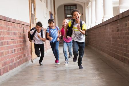 escuela primaria: Alumnos lindas corriendo por el pasillo en la escuela primaria