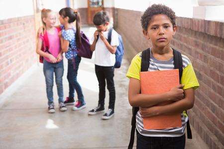 Pupils friends teasing a pupil alone in elementary school 写真素材