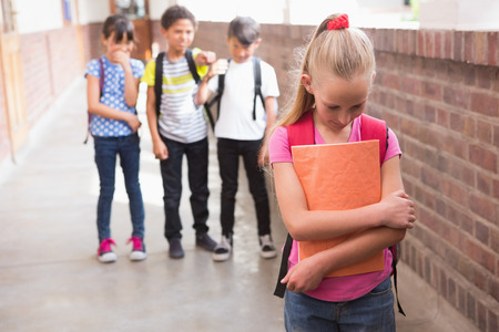 ni�os tristes: Alumnos amigos burlas a un alumno solo en la escuela primaria Foto de archivo