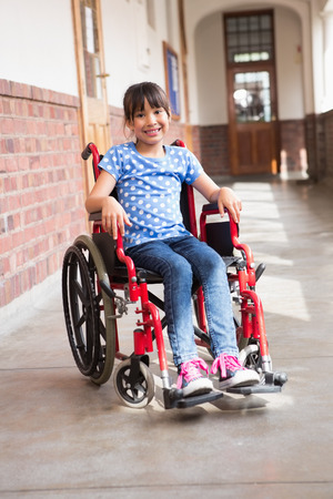 paraplegic: Lindo discapacitados sonriendo a la cámara en la sala en la escuela primaria alumno