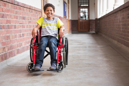 Cute disabled pupil smiling at camera in hall at the elementary school Stock Photo
