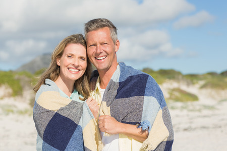 wrapped up: Happy couple wrapped up in blanket  at the beach Stock Photo