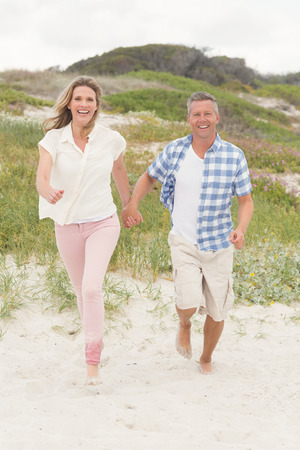 hands   free: Casual couple walking holding hands at the beach Stock Photo