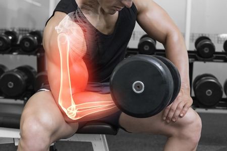 Digital composite of Highlighted arm of strong man lifting weights Stock Photo