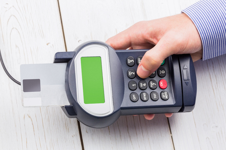 eftpos: Man entering his pin on terminal on a wooden table Stock Photo