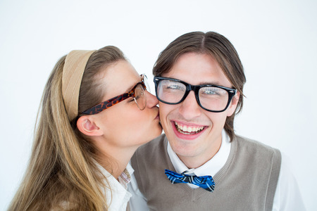 cheesy grin: Geeky hipster kissing her boyfriend on white background