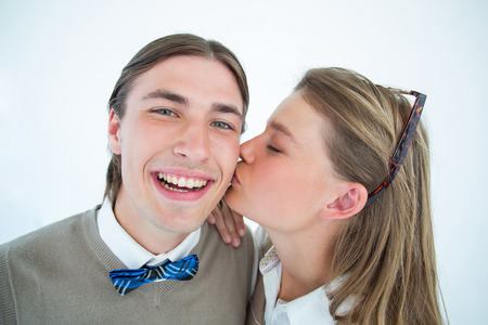 cheesy grin: Pretty geeky hipster giving boyfriend kiss on the cheek on white background
