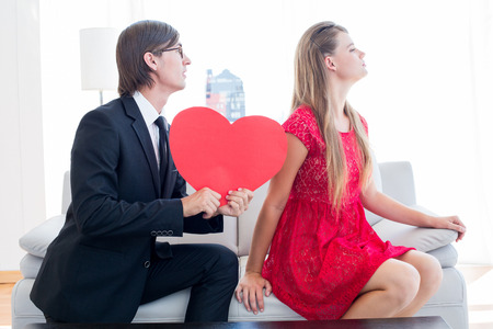 together with long tie: Cute geeky couple with red heart shape on the couch