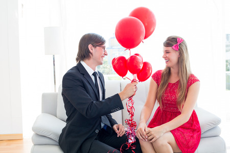 together with long tie: Cute geeky couple with red balloons on the couch