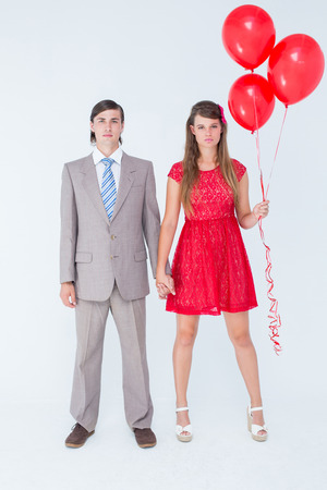 Unsmiling geeky couple standing hand in hand on white background photo