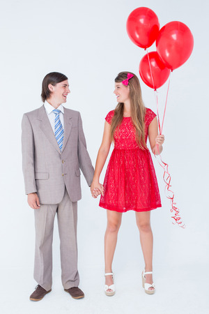 together with long tie: Smiling geeky couple standing hand in hand on white background