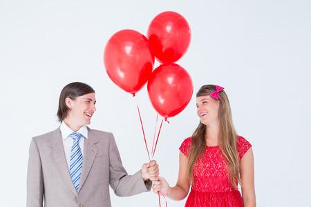 together with long tie: Sonriente pareja geek con globos rojos sobre fondo blanco