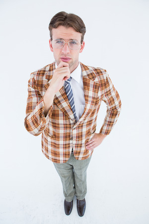 Geeky hipster thinking with hand on chin on white background photo